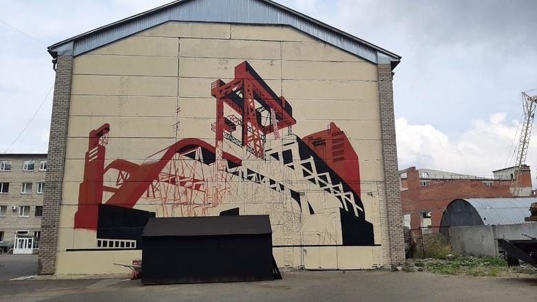 Стрит-арт-художник расписывает здание ТГАСУ в центре Томска